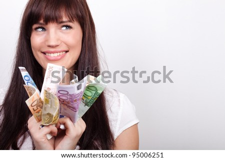 Happy young woman with her hands full of Euro bills - stock photo