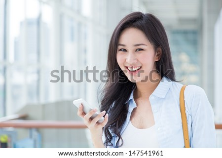 Happy young woman with her smart phone - stock photo