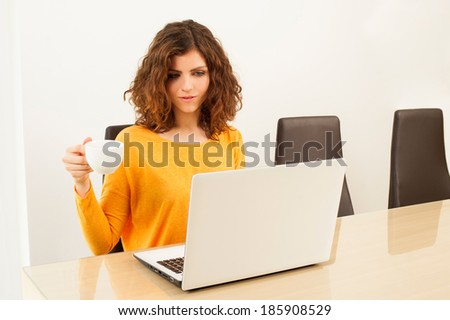 Happy young woman with laptop at home drinking coffee - stock photo