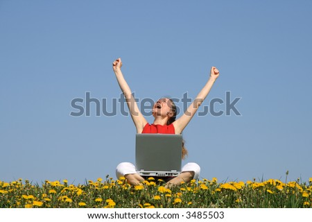 Happy young woman with laptop in a flowering spring field. - stock photo