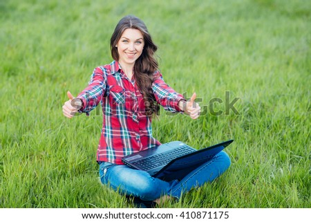Happy young woman with laptop sitting on grass in the blooming garden. Leisure in spring day. Toned image.