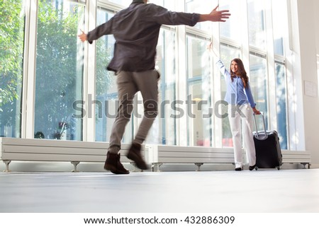 Happy young woman with luggage waving to her boyfriend. Man running with arms outstretched towards female partner at airport. She is with luggage at departure area. - stock photo