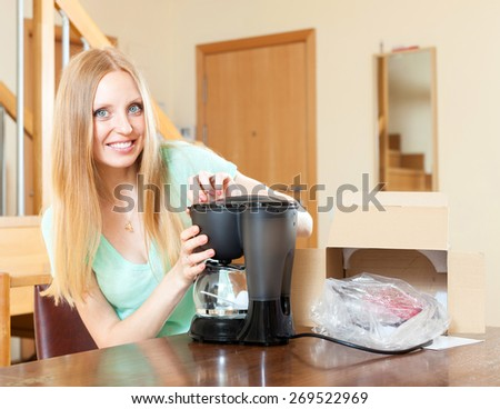 Happy young woman with new coffee machine at home in living room