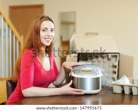 Happy young woman with new  slo-cooker at home