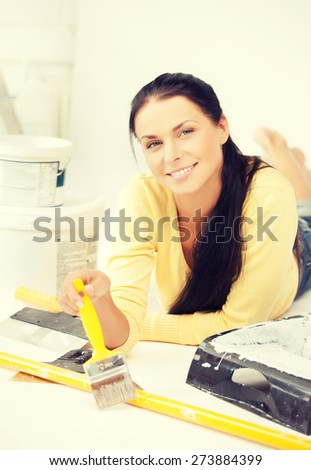 happy young woman with paintbrush and renovating tools - stock photo