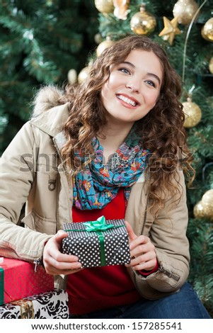 Happy young woman with presents sitting against Christmas tree in store - stock photo