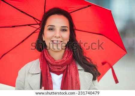 Happy young woman with red umbrella - stock photo
