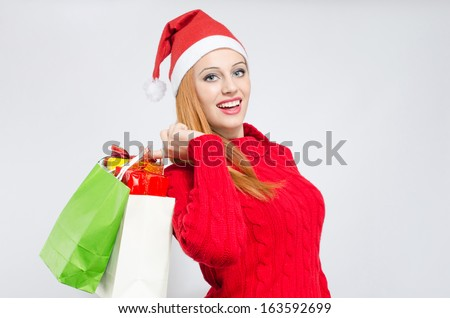 Happy young woman with Santa hat shopping for the Christmas holidays. Girl in red with many shopping bags and gifts.