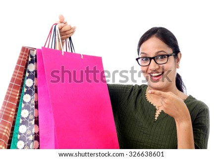 Happy young woman with shopping bags against white - stock photo