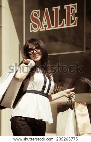 Happy young woman with shopping bags at the mall window  - stock photo