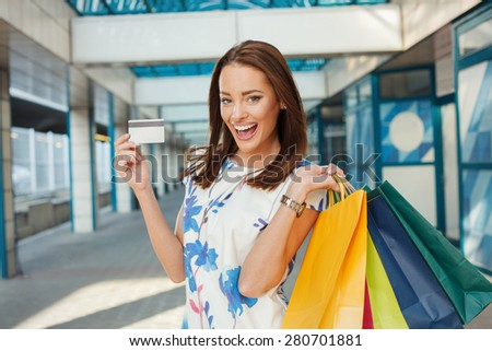 Happy young woman with shopping bags holding a credit card - stock photo