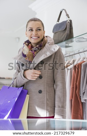 Happy young woman with shopping bags in store - stock photo