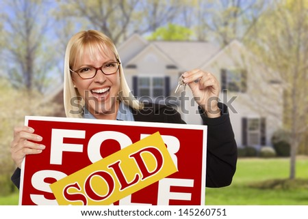 Happy Young Woman with Sold For Sale Real Estate Sign and Keys in Front of House.