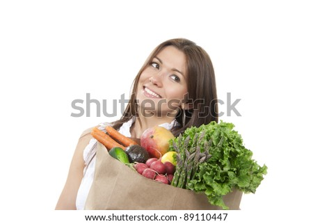 Happy young woman with supermarket shopping bag full of groceries, cucumbers, salad, asparagus, radish, avocado, lemon, mango, carrots on white background - stock photo