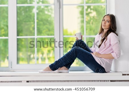 Happy young woman with tea - stock photo