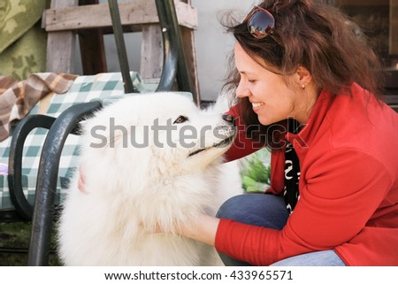 Happy young woman with white fluffy Samoyed dog - stock photo