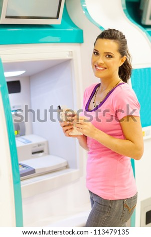 happy young woman withdrawing cash at an ATM - stock photo