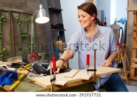 Happy young woman working in tinkering workshop. - stock photo
