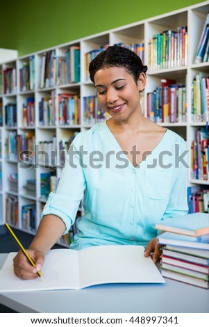 Happy young woman writing on notebook against bookshelf in library