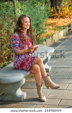 Happy young woman writing sms while sitting in city park