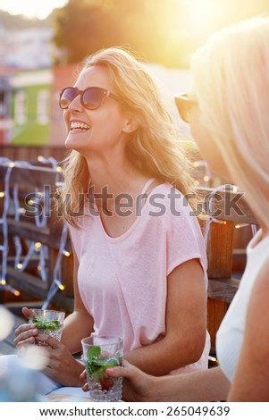 Happy young women chatting laughing outdoor on rooftop terrace - stock photo
