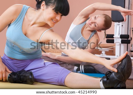 Happy young women exercising in sport club - stock photo