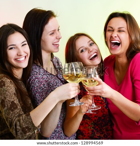 Happy young women friends touching the glasses with each other on party and have fun