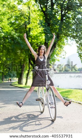 happy young women on bicycle with arms and legs raised expressing freedom and enthusiasm - stock photo