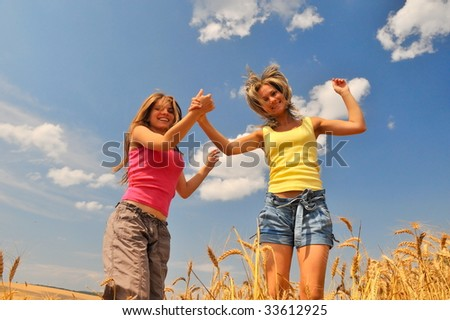 happy young women on field in summer