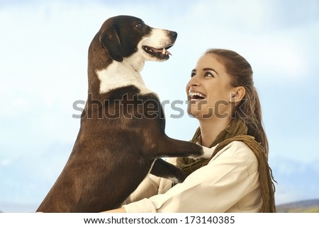 Happy young women playing with dog outdoors, laughing. - stock photo