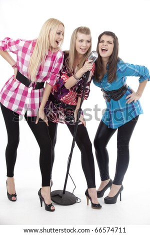Happy young women singing in a microphone - stock photo