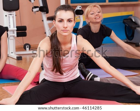 Happy young women stretching in fitness club