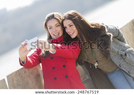 Happy young women taking photo with mobile phone - stock photo