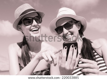 Happy young women using smart phone on the beach. Technology and beach concept. - stock photo