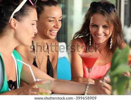 Happy young women with beverages having fun in cafe