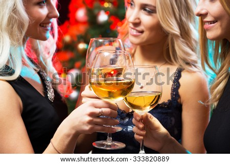 Happy young women with glasses of champagne. Xmas