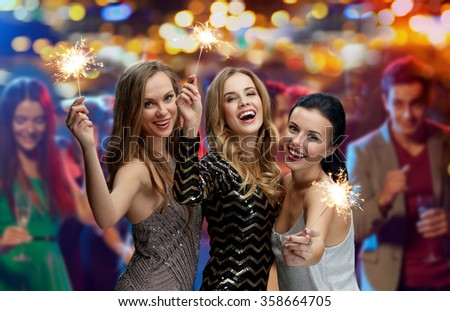 happy young women with sparklers at night club
