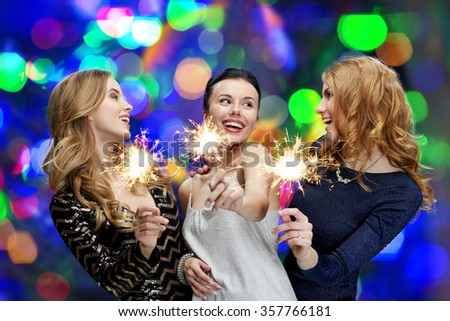 happy young women with sparklers over lights