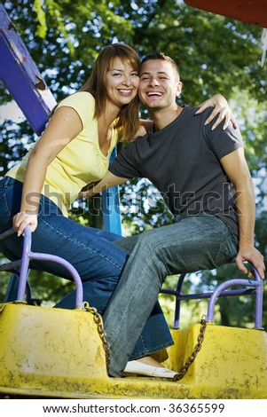Happy youngcouple on the carousel