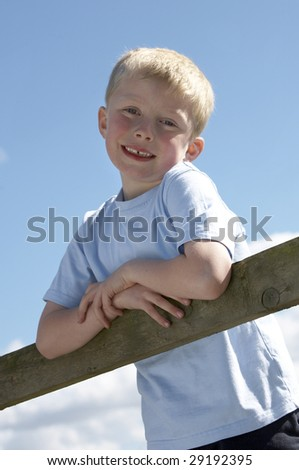 Happy, younger boy climbing on a fence in a park - stock photo