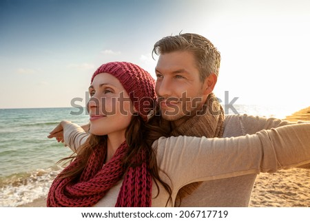 happy younger parents enjoying sundown seaside on the coast - stock photo