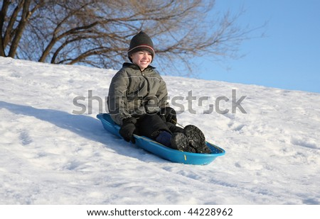 happy youth sledding down a snowy hill on a blue sled an smiling - stock photo