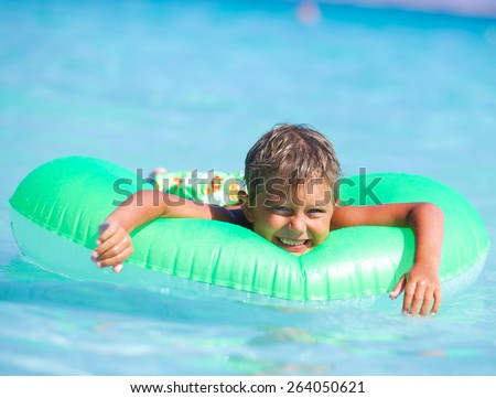 Happyboy playing on the inflatable rubber circle in the sea