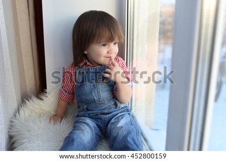 Happyy little boy (2 years) looks out of window in wintertime - stock photo