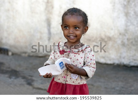 HARAR, ETHIOPIA - DECEMBER 25, 2012  Unidentified young smiling girl with the book on the streets.