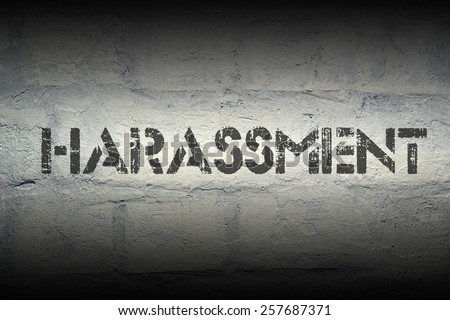 harassment stencil print on the grunge white brick wall - stock photo