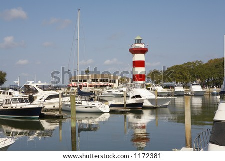 Harbor and lighthouse on a sunny day - stock photo