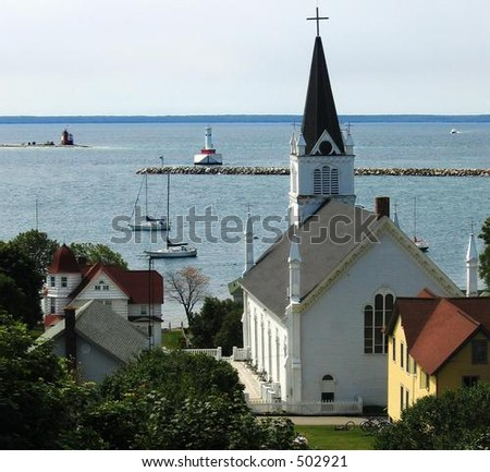 Harbor at Mackinac Island, Michigan with lighthouse and church - stock photo