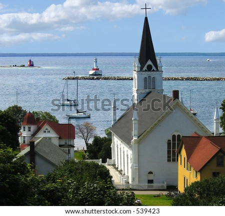Harbor at Mackinac Island with lighthouse, church and sailboats - stock photo