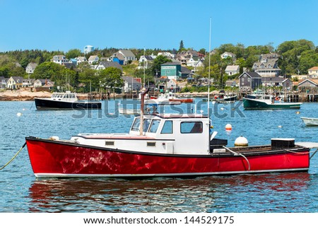 Harbor at Stonington, Maine, USA with a red lobster boat in the foreground - stock photo